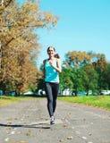 Funzionamento della giovane donna di forma fisica nel parco, nell'allenamento femminile del corridore - sport e nello stile di vi Fotografia Stock Libera da Diritti