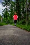 Funzionamento della giovane donna lungo il percorso curvo attraverso la foresta verde Immagine Stock