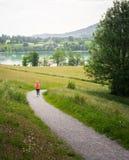 Funzionamento della giovane donna lungo il percorso curvo intorno al lago Tegernsee Fotografia Stock