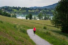 Funzionamento della giovane donna lungo il percorso curvo intorno al lago Tegernsee Immagini Stock