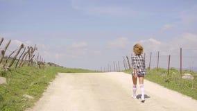 Funzionamento della giovane donna lungo una strada non asfaltata rurale archivi video