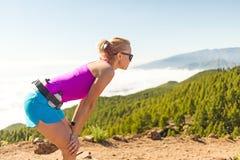 Funzionamento della giovane donna in montagne il giorno di estate soleggiato Immagini Stock