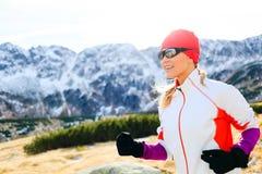 Funzionamento della giovane donna in montagne il giorno soleggiato di inverno Fotografie Stock Libere da Diritti