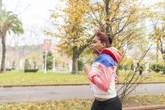 Funzionamento della giovane donna nel parco di autunno Fotografia Stock