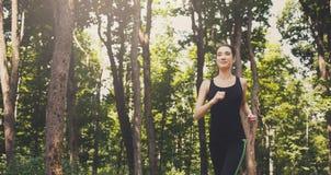 Funzionamento della giovane donna nel parco verde, spazio della copia Immagine Stock
