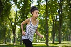 Funzionamento della giovane donna nel parco verde, spazio della copia Immagini Stock Libere da Diritti