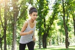 Funzionamento della giovane donna nel parco verde, spazio della copia Fotografie Stock