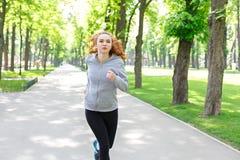Funzionamento della giovane donna nel parco verde, spazio della copia Fotografia Stock Libera da Diritti