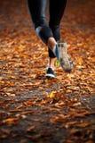 Funzionamento della giovane donna nelle foglie di autunno di prima serata Fotografia Stock
