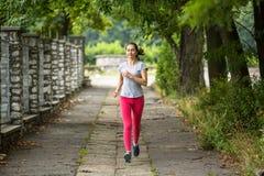 Funzionamento della giovane donna sulla pista attraverso il parco di estate Fotografia Stock Libera da Diritti