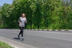 Funzionamento della giovane donna sulla strada, spazio della copia Immagini Stock Libere da Diritti