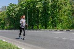 Funzionamento della giovane donna sulla strada, spazio della copia Fotografia Stock