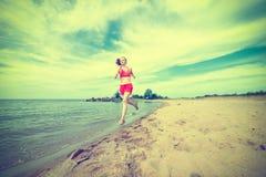 Funzionamento della giovane signora alla spiaggia di sabbia soleggiata di estate Fotografia Stock