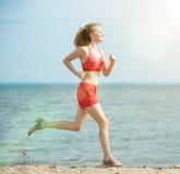 Funzionamento della giovane signora alla spiaggia di sabbia soleggiata di estate workout trotto immagine stock