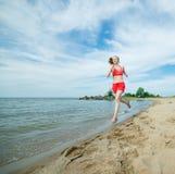 Funzionamento della giovane signora alla spiaggia di sabbia soleggiata di estate workout trotto fotografie stock libere da diritti