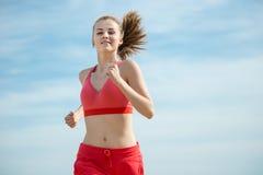 Funzionamento della giovane signora alla spiaggia di sabbia soleggiata di estate workout trotto fotografia stock libera da diritti