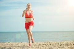 Funzionamento della giovane signora alla spiaggia di sabbia soleggiata di estate workout trotto immagini stock libere da diritti