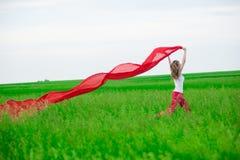 Funzionamento della giovane signora con il tessuto nel campo verde Donna con la sciarpa Immagine Stock Libera da Diritti