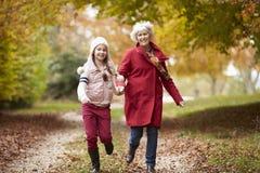 Funzionamento della nonna lungo Autumn Path With Granddaughter Fotografia Stock