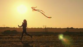 Funzionamento della ragazza di bellezza con l'aquilone al tramonto stock footage