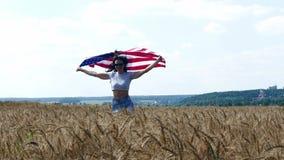 Funzionamento della ragazza di bellezza sul giacimento di grano giallo con la bandiera nazionale degli Stati Uniti video d archivio