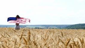 Funzionamento della ragazza di bellezza sul giacimento di grano giallo con la bandiera nazionale degli Stati Uniti archivi video
