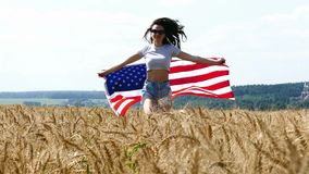 Funzionamento della ragazza di bellezza sul giacimento di grano giallo con la bandiera nazionale degli Stati Uniti stock footage