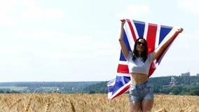 Funzionamento della ragazza di bellezza sul giacimento di grano giallo con la bandiera nazionale della Gran Bretagna video d archivio
