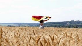 Funzionamento della ragazza di bellezza sul giacimento di grano giallo con la bandiera nazionale tedesca video d archivio