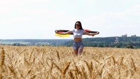 Funzionamento della ragazza di bellezza sul giacimento di grano giallo con la bandiera nazionale tedesca archivi video
