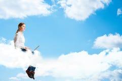 Funzionamento della ragazza nelle nuvole con un computer portatile Immagini Stock Libere da Diritti