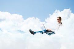 Funzionamento della ragazza nelle nuvole con un computer portatile Fotografia Stock