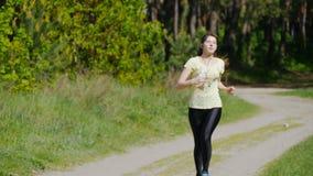 Funzionamento della ragazza sul sentiero nel bosco in un parco e sul respiro di presa dopo avere pareggiato Ritratto della donna  archivi video