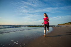 Funzionamento della ragazza sulla spiaggia Fotografie Stock Libere da Diritti
