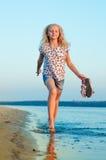 Funzionamento della ragazza sulla spiaggia all'acqua a piedi nudi Fotografie Stock