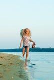 Funzionamento della ragazza sulla spiaggia all'acqua a piedi nudi Fotografia Stock Libera da Diritti