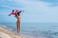 Funzionamento della ragazza sulla spiaggia con la bandiera del sindacato Fotografie Stock