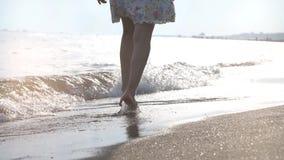 Funzionamento della ragazza sulle onde al tramonto sulla spiaggia sabbiosa Concetto di felicità stock footage