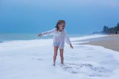 Funzionamento della ragazza sulle onde in una tempesta sulla costa del mare Fotografia Stock