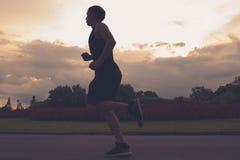 Funzionamento della siluetta dell'atleta del corridore nel parco pubblico concetto pareggiante di benessere di allenamento di alb Immagini Stock