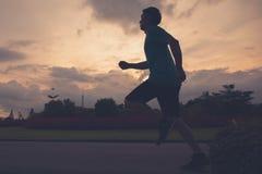 Funzionamento della siluetta dell'atleta del corridore nel parco pubblico concetto pareggiante di benessere di allenamento di alb Fotografia Stock