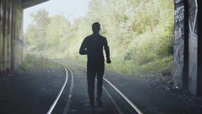 Funzionamento della siluetta dell'uomo del movimento lento sulle piste del treno Vista posteriore Colpo astratto di conclusione d video d archivio