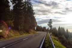 Funzionamento della strada asfaltata lungo il pendio invaso con la foresta di conifere Fotografia Stock