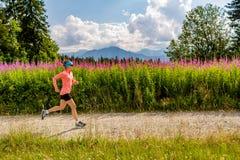 Funzionamento della traccia della donna sulla strada campestre in montagne, giorno di estate Immagini Stock