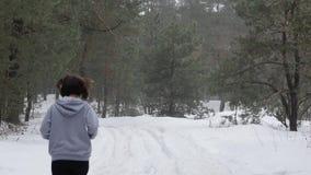 Funzionamento della traccia Giovani ragazze caucasiche attraenti che corrono nella foresta sulla neve Indietro segua il colpo archivi video