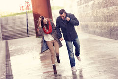 Funzionamento delle coppie nella pioggia fotografie stock