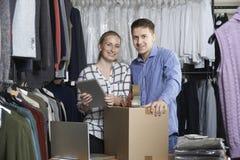 Funzionamento delle coppie sulla linea merci dell'imballaggio del negozio di vestiti per spedizione Fotografie Stock