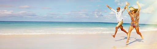 Funzionamento delle coppie sulla spiaggia fotografie stock