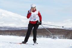 Funzionamento dello sciatore della sportiva lungo la pista dello sci di inverno e parlare sullo smartphone Fotografia Stock Libera da Diritti