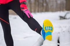 Funzionamento di inverno nel parco: primo piano degli abiti sportivi in neve, donna che allungano prima del trotto, forma fisica  Immagini Stock Libere da Diritti